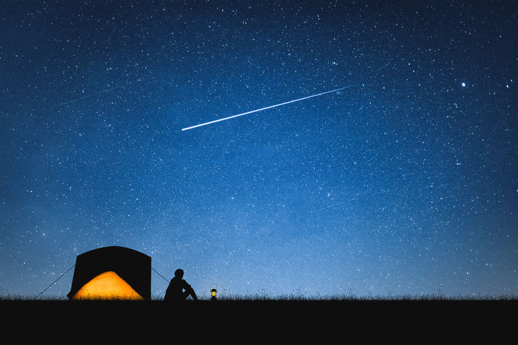 Silhouette person camping on field against star field