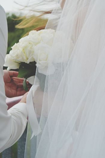 Cropped Hands Of Groom Giving Bouquet To Bride