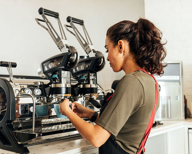 Side view of woman using coffee at home