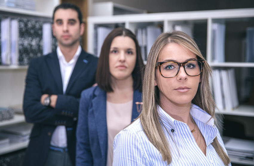 Close up of businesswoman looking at camera with two colleagues in the background Business Company Horizontal Man Office Teamwork Woman Working Workplace Business Finance And Industry Businessman Businesswoman Caucasian Chairman Chief Female Headquarters Male People Portrait Professional Seriousface Sucess Team Three People