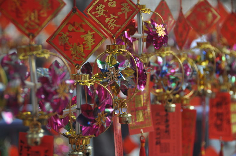 Close-up of decorations hanging in market for sale