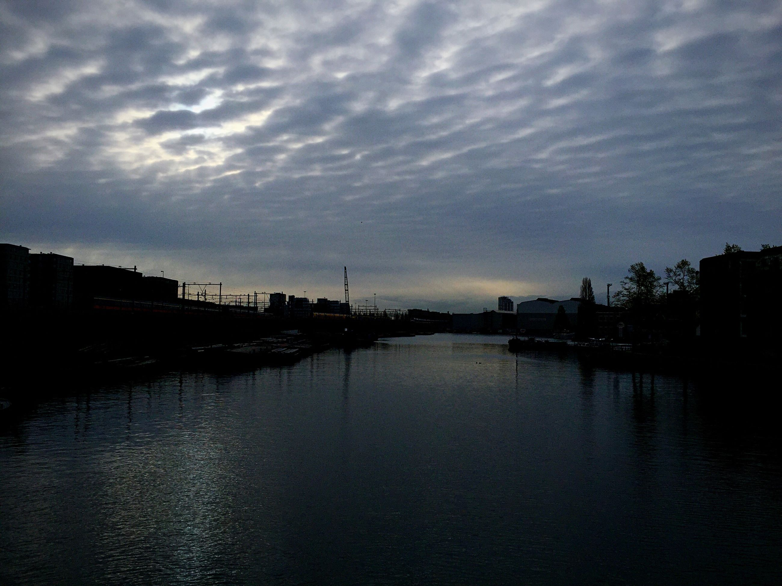 water, sky, cloud - sky, waterfront, cloudy, tranquil scene, scenics, sunset, tranquility, reflection, building exterior, built structure, silhouette, beauty in nature, architecture, cloud, nature, sea, lake, dusk