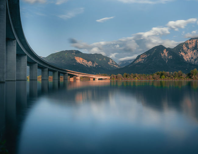 Scenic view of lake with bridge against sky
