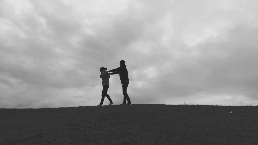 Low Angle View Of Man And Woman Walking On Hill Against Cloudy Sky At Dusk