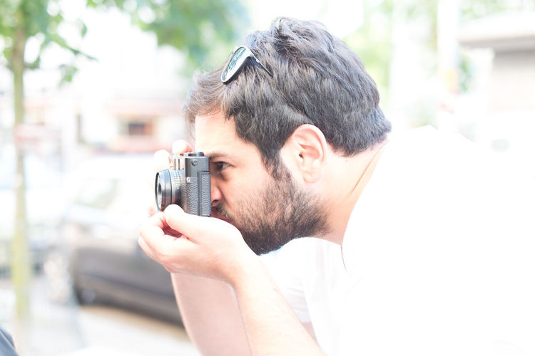 Side view of young man photographing through digital camera