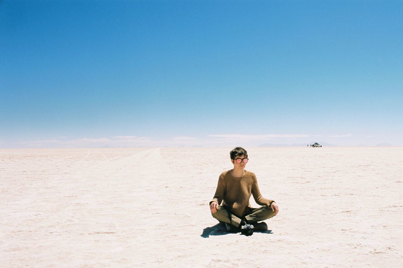 Full Length Of Woman Sitting On Sand At Desert Against Clear Blue Sky During Sunny Day