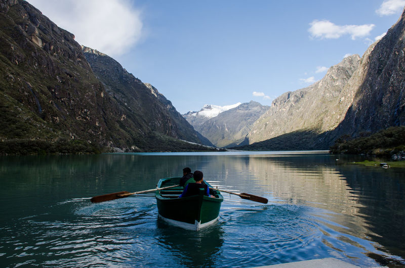 Boating In Calm Lake Against Mountain Range