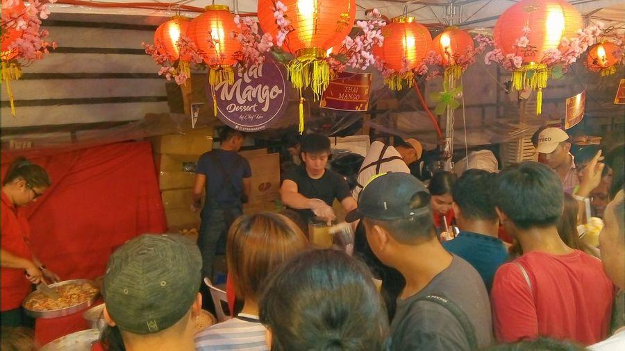 Group of people at illuminated market stall
