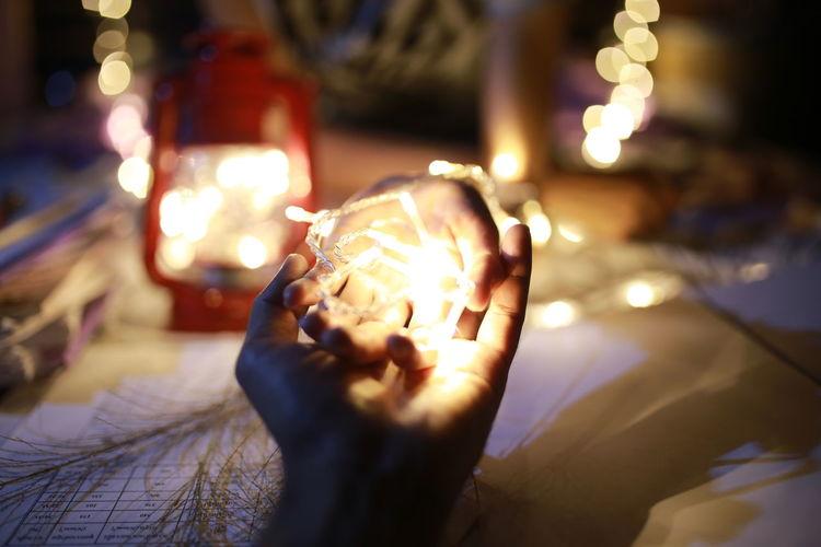 Close-up of hands holding illuminated lighting equipment