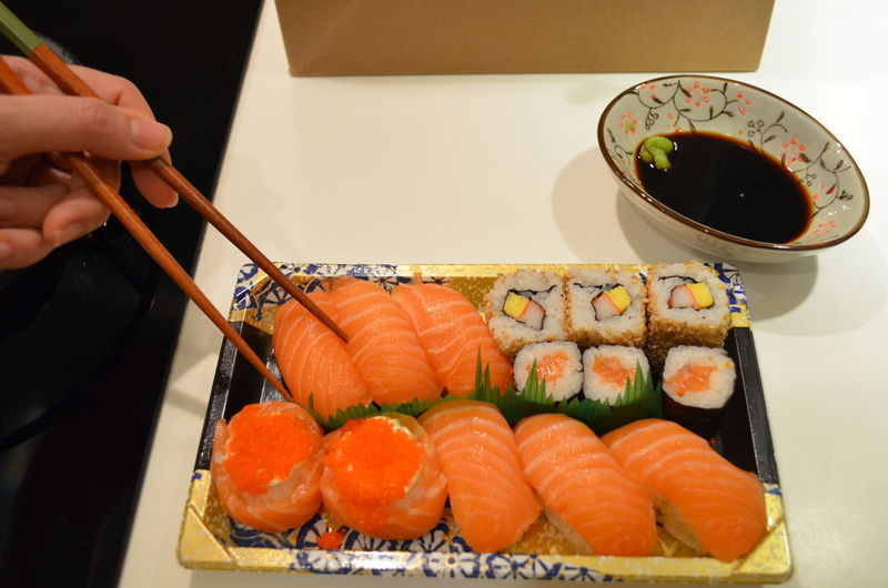 Cropped image of hand holding salmon sushi with chopsticks