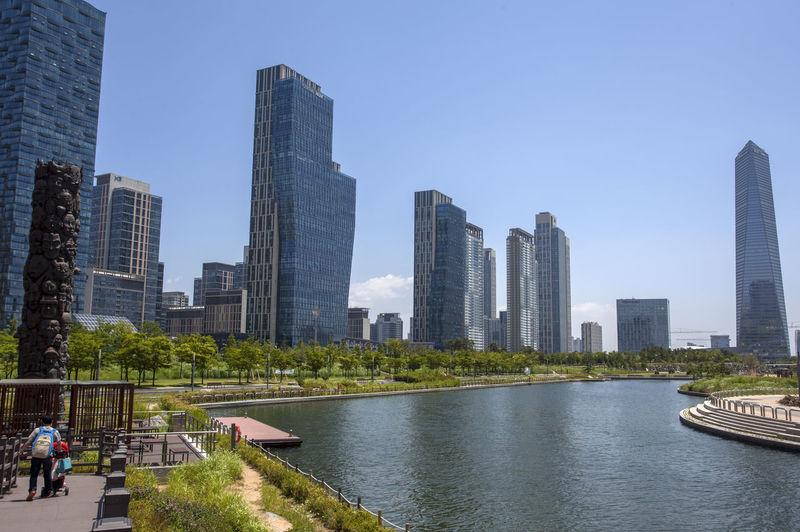 View Of Lake By Modern Buildings Against Blue Sky