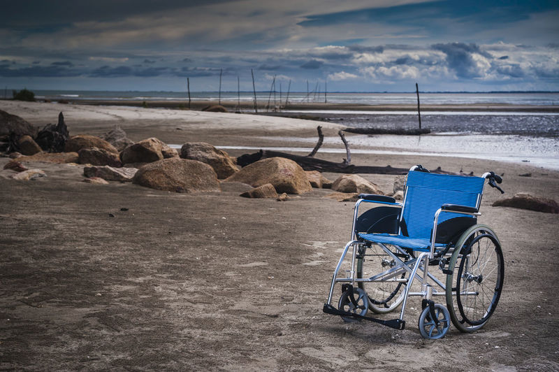 Wheelchair on beach against cloudy sky