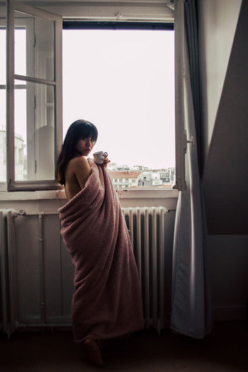 Side View Of Woman Wrapped In Blanket Having Coffee While Standing By Window
