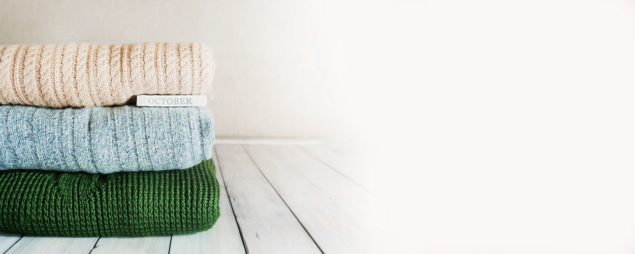 Cozy autumn banner stack of warm knitted sweaters in pastel colors and the inscription october
