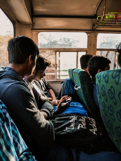 Rear view of men sitting in bus