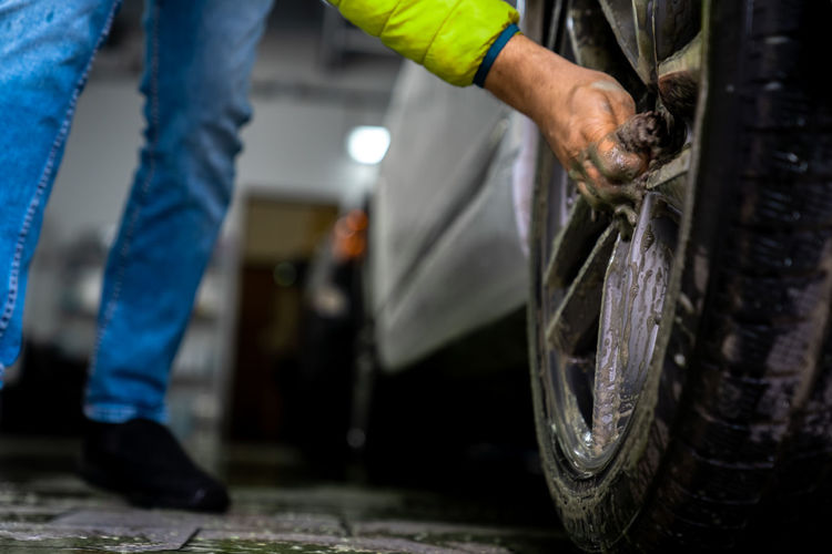 Low section of man cleaning tire at garage
