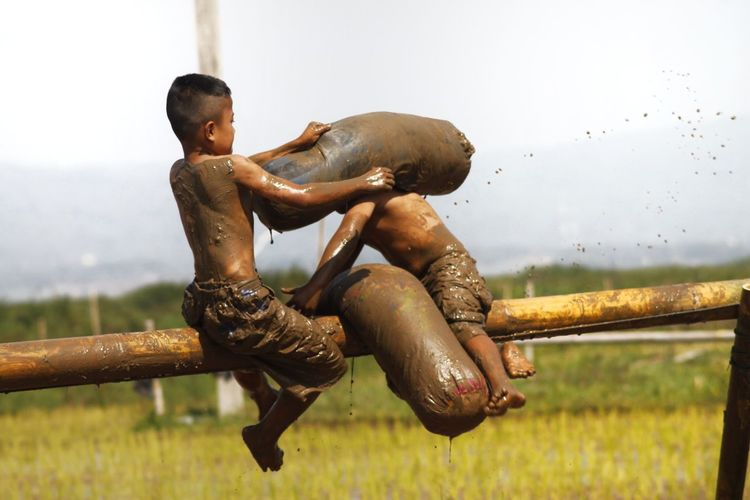 Messy shirtless boys fighting while sitting on bamboo against sky
