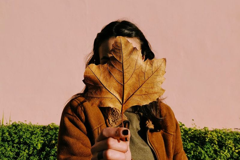 Portrait of person holding leaf against sky during autumn