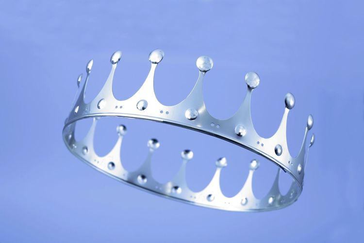 Low angle view of crown against purple background
