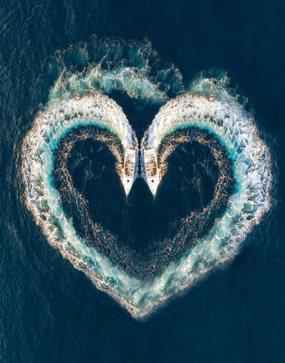 Heart shape formed with water wake in sea