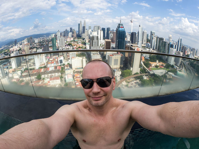 Portrait of shirtless man smiling at balcony against cityscape