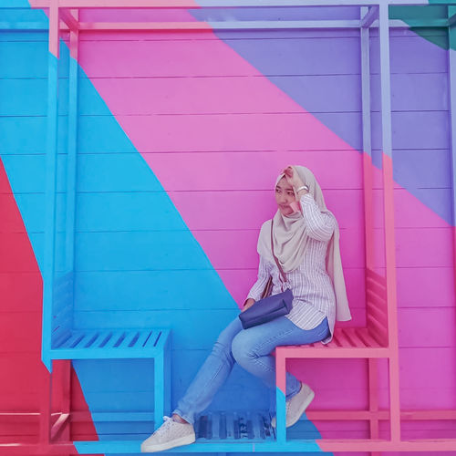 Woman sitting against pink wall