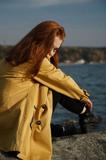 Beautiful woman in coat sitting at beach