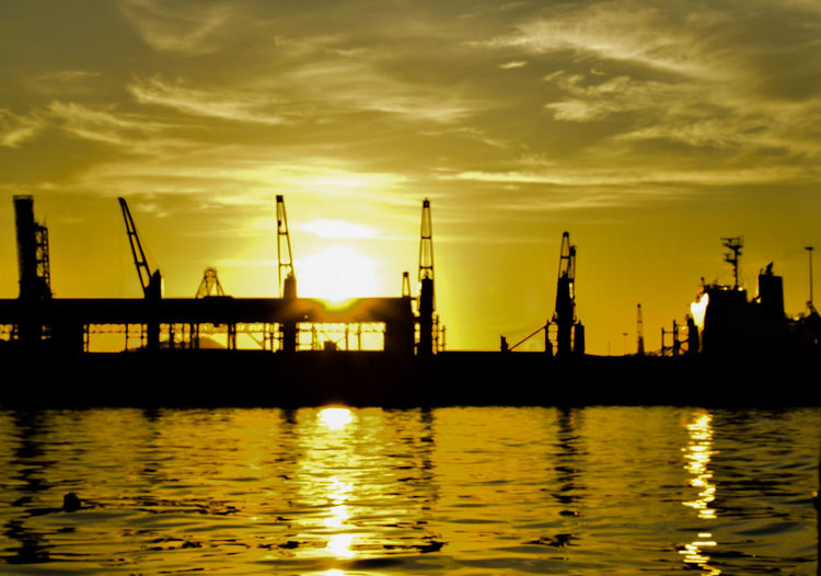 Silhouette cranes at pier against sky during sunset