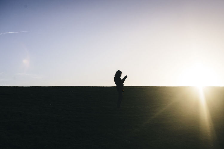 Young man taking picture of Sunset Silhouette Sky One Person Full Length Real People Sunlight Lifestyles Nature Land Leisure Activity Adult Beauty In Nature Day Outdoors Lens Flare Sun Sunbeam Photography Photographer