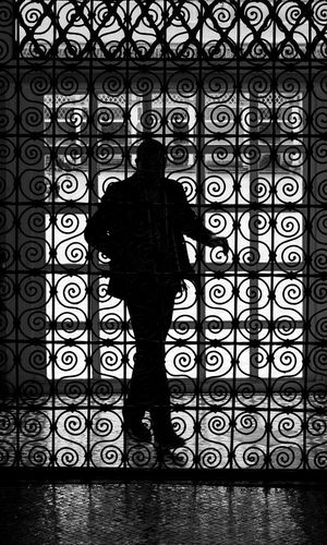 Silhouette man standing at corridor of building