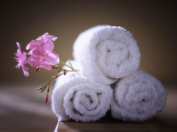 Close-up of pink flowers with towels on table