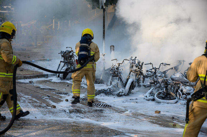Rear view of firefighters extinguishing burning motorcycles on road in city