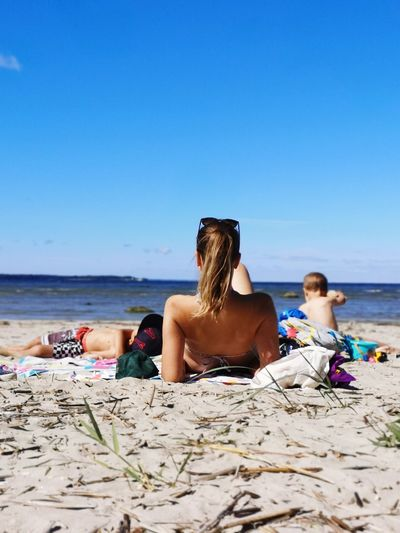 Rear view of mother with kids relaxing on beach against sky