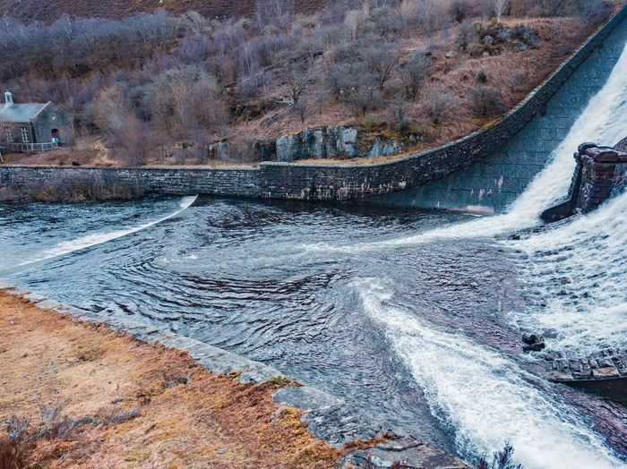 water pouring out of a dam Outpouring Waterfall Dam Power Generation Escape Stream Clean Water Water Supply Victorian Architecture Victorian Engineering British Wales UK Winter Bare Trees Flowing Water Flowing Stream Foam Whirpool Speed сток Water High Angle View Backgrounds Shore Rocky Mountains LINE Wave Crashing Rugged Rushing