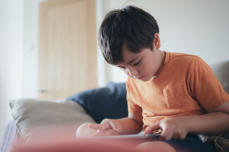 Boy looking away while sitting at home