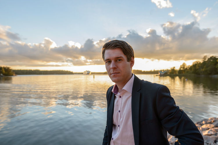 Portrait of young man standing by lake against sky during sunset
