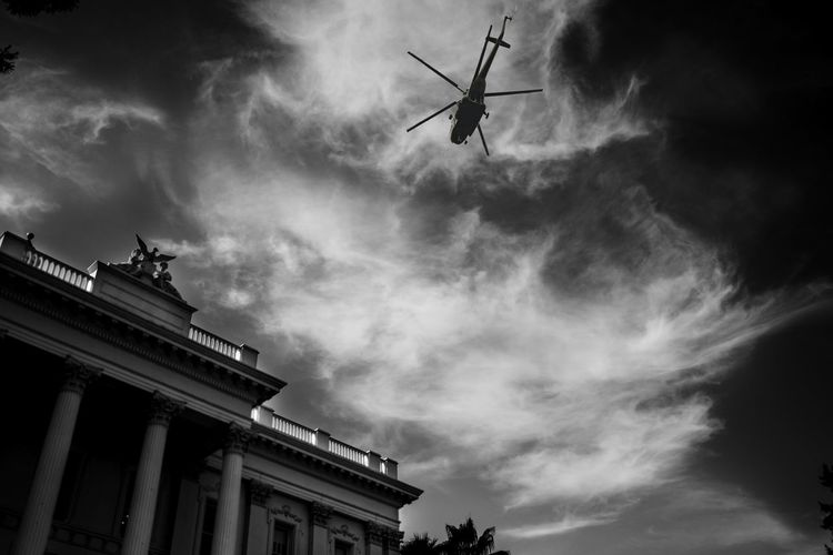 Low angle view of helicopter against clouds