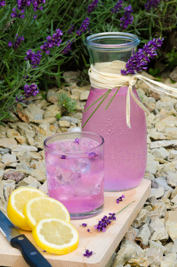 High angle view of pink drink by lemon on cutting board in back yard