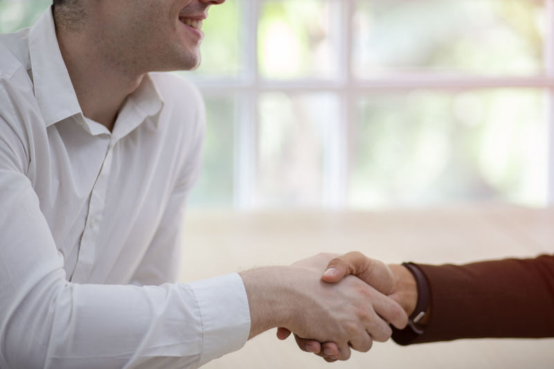 Midsection of business people shaking hands
