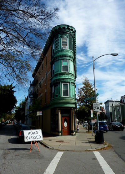 Small wedge shaped building with fantastic curved copper front at corner of Pleasant St and River, Boston Architecture Blue Sky Building Exterior Built Structure City Copper  Day No People Outdoors Road Road Closed Road Sign Sky Sky And Clouds Tree The Graphic City