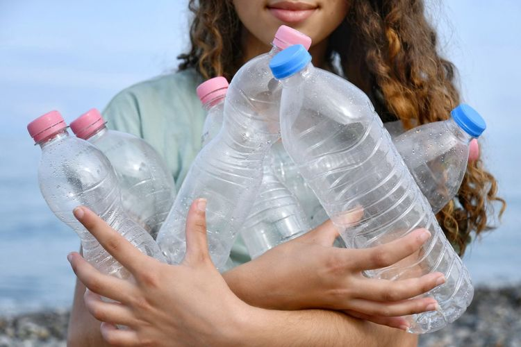 Midsection of woman drinking water in bottle