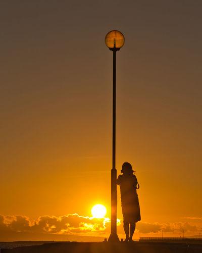 Silhouette man photographing street light against orange sky