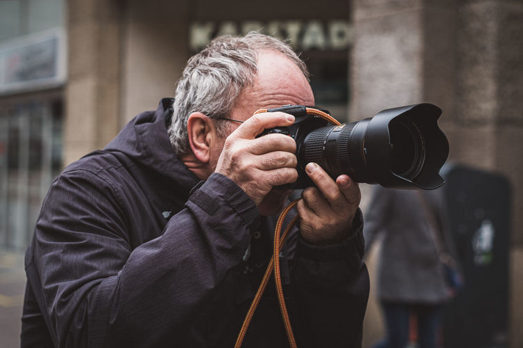 Man photographing while standing in city