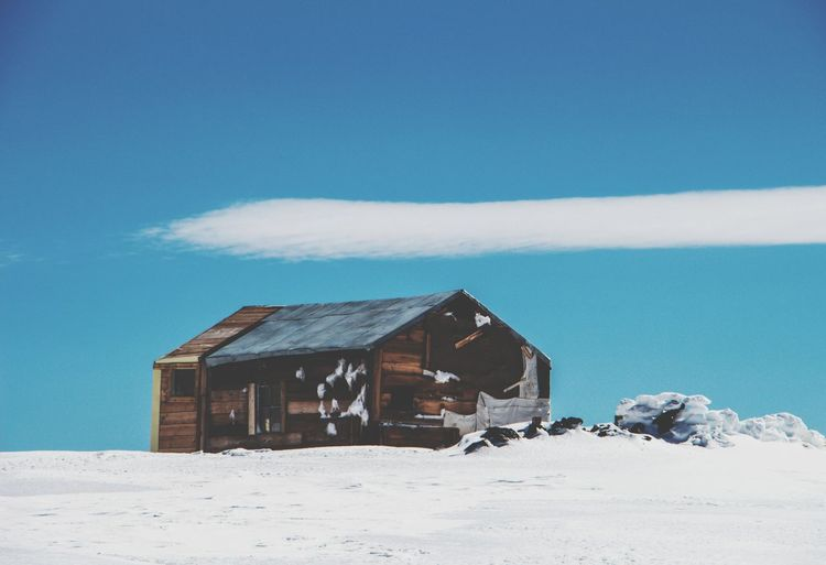 Houses on snow covered land against blue sky