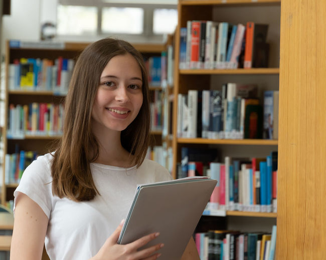 Portrait of smiling teenage girl holding file while standing in library
