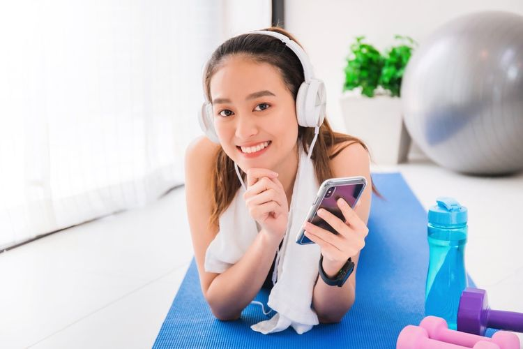 Portrait of smiling girl using mobile phone at home