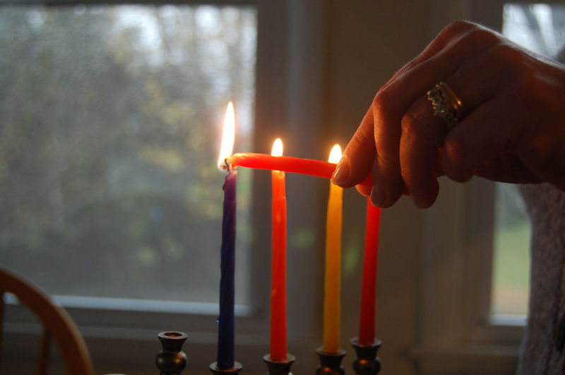 Cropped image of woman igniting candles on hanukkah at home
