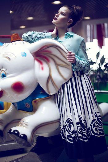 Female model posing on elephant sculpture