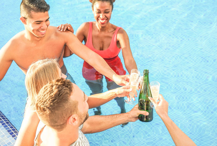 Happy friends toasting drinks in swimming pool