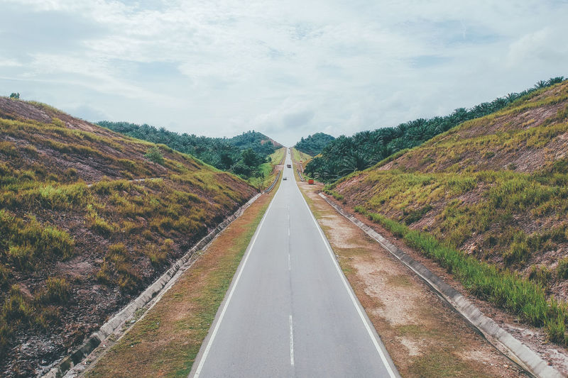 View from above, a rural road in Malaysia Beauty In Nature Cloud - Sky Day Diminishing Perspective Direction Dividing Line Landscape Long Marking Mountain Nature No People Outdoors Plant Road Road Marking Sign Sky Symbol The Way Forward Transportation Tree vanishing point